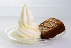 Brownie with ice cream. Chocolate brownie with caramel sauce and vanilla yogurt ice cream served on a transparent plate Royalty Free Stock Photo