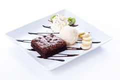 Brownie and ice cream with whipping cream and banana slices Royalty Free Stock Photography