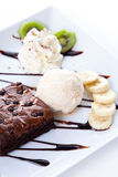 Brownie and ice cream with whipping cream and banana slices Stock Photos