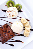 Brownie and ice cream with whipping cream and banana slices Stock Images