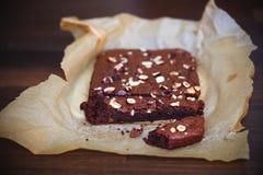 Brownie met hazelnoten, voor het eten, in bakseldocument dat worden gesneden Royalty-vrije Stock Fotografie