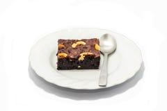 A brownie no prato branco com uma colher para que pronto serva Fotos de Stock Royalty Free