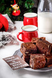 Brownie pieces with nuts on the plate, two cups of milk and bottle. Christmas tree. Stock Photo