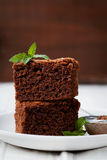 Brownie stack, closeup chocolate cake in plate on rustic table Royalty Free Stock Photos