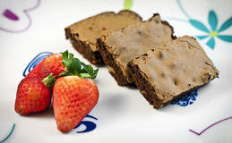 Brownie and strawberries. On a white plate with drawings Royalty Free Stock Photos