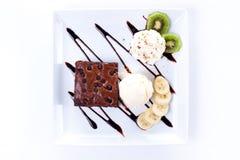 Brownie y helado con las rebanadas de la nata montada y del plátano Fotos de archivo libres de regalías