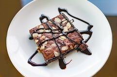 Brownies με το καυτό φοντάν αμυγδάλων και σάλτσα σοκολατών που εξυπηρετείται στο α Στοκ Φωτογραφία