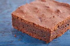 Brownies caseiros do chocolate na obscuridade - fundo azul Imagem de Stock