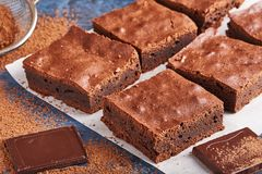 Brownies caseiros do chocolate na obscuridade - fundo azul foto de stock royalty free