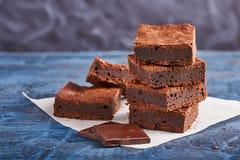 Brownies caseiros do chocolate na obscuridade - fundo azul Imagem de Stock Royalty Free