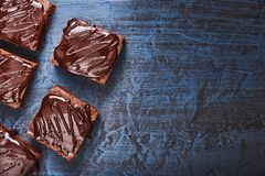 Brownies caseiros do chocolate na obscuridade - fundo azul, vista superior Imagem de Stock