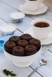 Brownies do chocolate e um copo do chá na tabela de madeira Fotografia de Stock