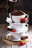 Brownies em uns copos de café empilhados com molho de chocolate Fotos de Stock
