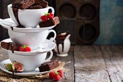 Brownies em uns copos de café empilhados com molho de chocolate Imagens de Stock