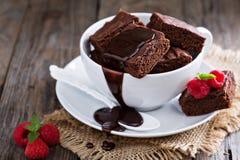 Brownies em uns copos de café empilhados com molho de chocolate Fotografia de Stock