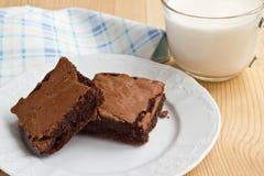 Brownies op een plaat met een kop van melk Stock Afbeelding