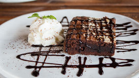 Brownies topped with chocolate and whipped cream. Royalty Free Stock Photography
