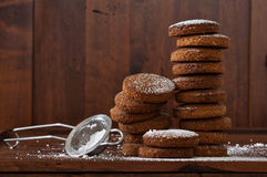 Biscuit tower of whole wheat flour, oats, hazelnuts and stainer for icing sugar Stock Photos