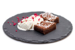 Brownies with vanilla ice-cream isolated on white. 2 pieces of fresh homemade brownies with licorice vanilla ice-cream and dehydrated raspberries on rough Royalty Free Stock Photos