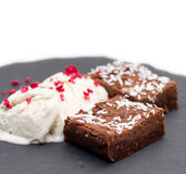 Brownies with vanilla ice-cream isolated on white. 2 pieces of fresh homemade brownies with licorice vanilla ice-cream and dehydrated raspberries on rough Stock Photos