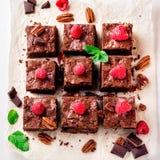 Browniestukken met noten met bessen en muntbladeren worden verfraaid op het Witboek dat stock foto