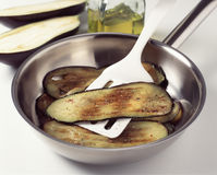 Browning the sliced eggplants Stock Photos