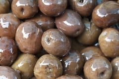 Brownish olives in oil close up. Royalty Free Stock Image