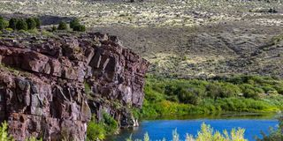 The Green River flows through Browns Park NWR in Colorado. The Green River looks blue at this scenic spot beside a tall bluff in Browns Park National Wildlife stock photo