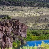 The Green River flows through Browns Park NWR in Colorado. The Green River looks blue at this scenic spot beside a tall bluff in Browns Park National Wildlife royalty free stock photo