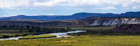 The Green River flows through Browns Park NWR in Colorado. Panorama of the Green River, which looks blue as it flows through lush wetlands in Browns Park stock image
