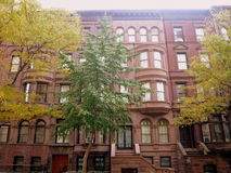 Brownstone Apartments Manhattan. The warm colors of a brownstone building against the colrs of the fall stock photo