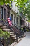 Brownstone houses in urban residential neighborhood of Brooklyn, NYC. Stairway with an American flag by the brownstone houses in urban residential neighborhood Stock Images