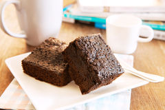 Browny cake ready to eat on white dish with coffee cup and magaz Stock Photo