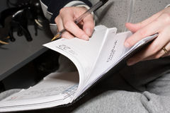 Browse through diary. Girl turning the pages on her diary Stock Image