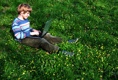 Browser (Child with notebook sit green grass) Royalty Free Stock Image
