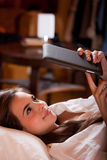 Browsing in bed. Cute young brunette  using tablet computer laying in bed Royalty Free Stock Images