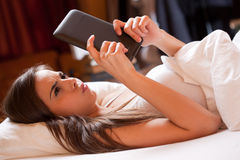 Browsing in bed. Cute young brunette  using tablet computer laying in bed Stock Photos