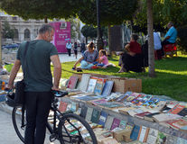 Browsing books for sale in park at Piata Universitatii, Buchares. A cyclist stops to look at books being sold on the pavement at Piata Universitatii (University stock image