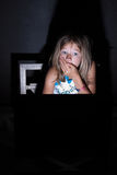 Browsing in the dark. Young blond girl sitting in the dark in front of a laptop computer with shocked expression royalty free stock photos