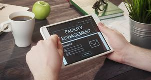 Browsing facility management web page using digital tablet at desk stock video footage