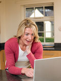 Browsing the Internet. Surprised Woman Browsing the Internet on Laptop in Kitchen Stock Photography