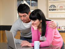 Browsing the Internet. Couple Browsing the Internet on Laptop in Kitchen Royalty Free Stock Image