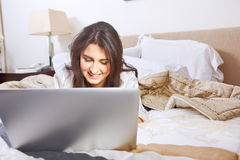 Browsing internet on bed Stock Photo