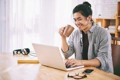 Browsing internet. Joyful Asian man drinking coffee and browsing internet Royalty Free Stock Image