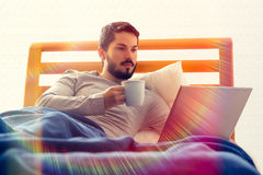Browsing the internet, lying in bed. Male browsing the internet in bed. Morning, color filter, lens flare, cup of coffee Royalty Free Stock Photos