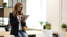 Browsing Online on Tablet by Businesswoman Sitting on Desk. Young Designer , Creative Designer stock video footage