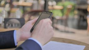 Browsing on Smartphone in Outdoor Cafe. The Browsing on Smartphone in Outdoor Cafe, high quality stock video footage