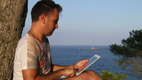 Browsing Tablet Next to the Sea Royalty Free Stock Photo