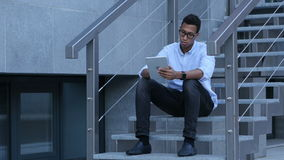 Browsing on Tablet PC while Young Black Man Sitting on Stairs. Creative designer , businessman stock footage