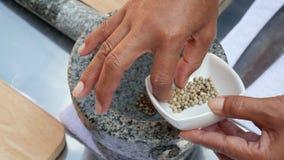 Broyage de poivre en mortier en pierre avec le pilon pour la sauce chili tha?landaise Femme pr?parant la sauce pour l'igname tha? banque de vidéos
